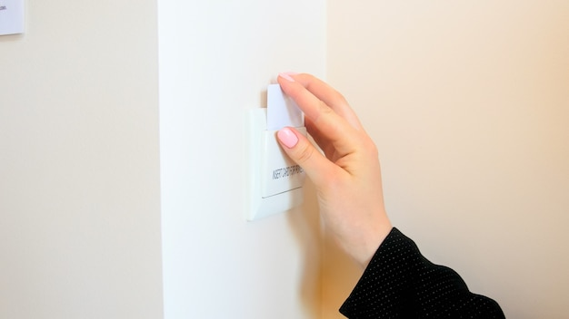 Female hand inserting electronic key card in hotel room electric switch.