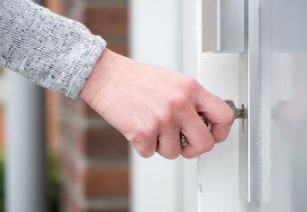 Female hand inserting key in door