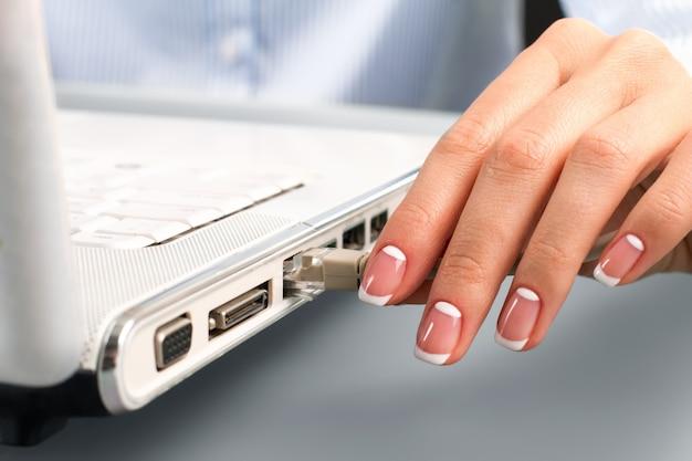 Lan 케이블을 삽입하는 여성 손. 숙녀의 손은 lan 케이블을 삽입합니다. 인터넷 서핑을 해보자. 새로운 소프트웨어를 다운로드할 시간입니다.