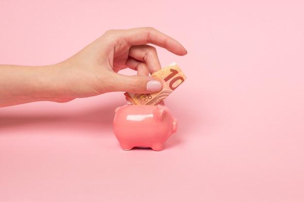 Female hand inserting a ten euro bill into a pink ceramic piggy bank