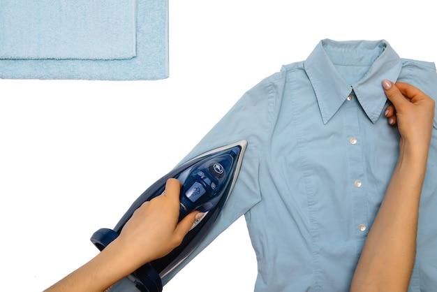 隔離された女性の手アイロン服上面図。家事中に上から見たアイロンアイロン男性のシャツを着た若い女性。白いテーブルの上の青い鉄。
