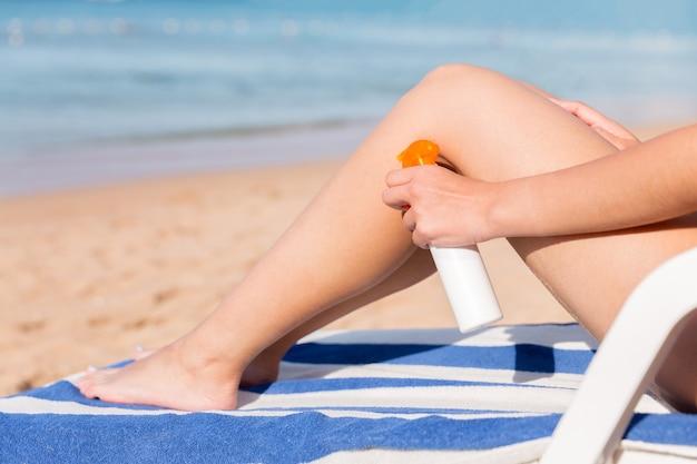 여성의 손은 그녀의 부드러운 검게 그을린 다리에 자외선 차단제를 바르고 있습니다. 스킨 케어 개념.