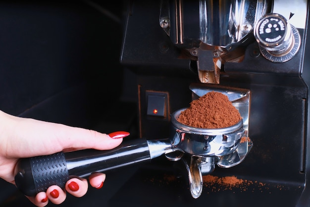 In the female hand is a coffee holder, the coffee beans are poured into the filter