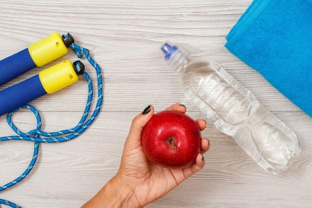 女性の手は、縄跳び、水のボトル、タオルを背景に部屋やジムで赤いリンゴを持っています。フィットネスのためのツール。上面図。