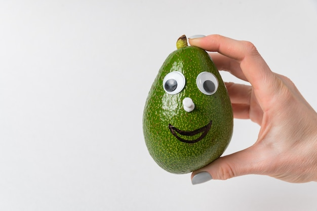 Female hand is holding an avocado-smiley on white background. avocado character with funny face