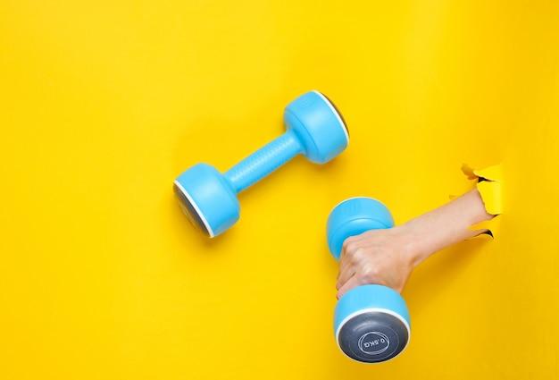女性の手は引き裂かれた黄色い紙を通して青いプラスチックダンベルを持っています。ミニマルスポーツコンセプト