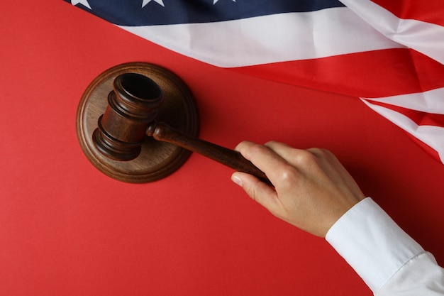 Female hand judge holds gavel on red background with american flag