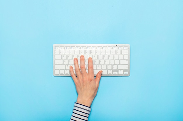 Female hand on a keyboard on a blue surface. concept of office work, freelance, online. . flat lay, top view