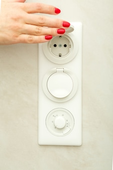 여성 손으로 전기 콘센트의 보호 덮개를 들어 올립니다.