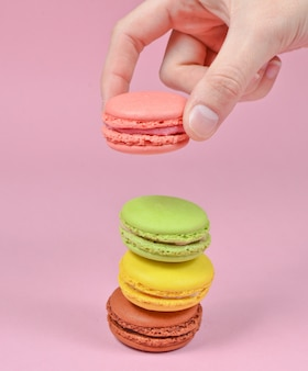 여성 손 핑크 마카롱 쿠키를 낮 춥니 다. 핑크 파스텔 배경에 마카롱의 스택. 미니멀리즘