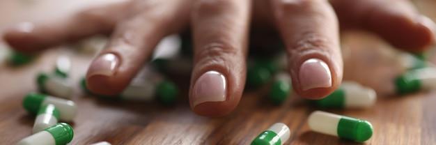 Женская рука лежа на крупном плане разбросанных капсул. концепция передозировки наркотиков
