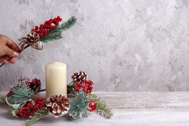 女性の手は、キャンドル、コーン、ベリー、クリスマスツリーの枝、モックアップ、カードの花輪を作ります。