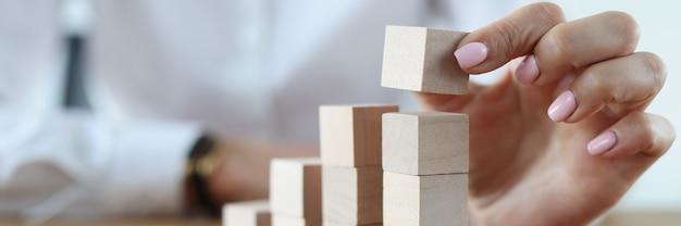 女性の手が塔で木製の立方体を作る