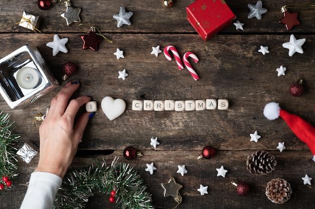 Женская рука делает я люблю рождественский знак на деревянных кубиках