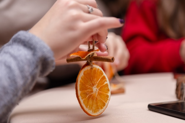 Female hand making decorations from dried oranges, stars from tangerine and cinnamon