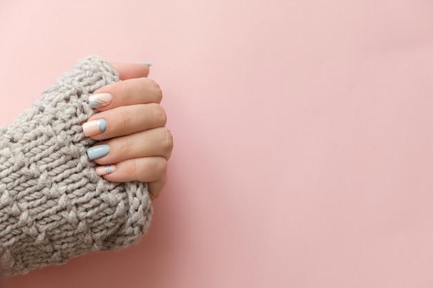 女性の手のマニキュアはニットセーターでビューを閉じます。トレンディな幾何学的なネイルアートマニキュア。マニキュアサロンバナーコンセプト