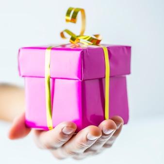 생일이나 크리스마스 선물 상자를 제공하는 여성의 손. 얕은 dof.