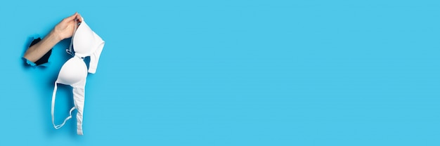 새로운 흰색 브래지어를 들고 파란색 배경에 여성 손