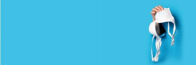 흰색 브래지어를 들고 파란색 배경에 여성 손