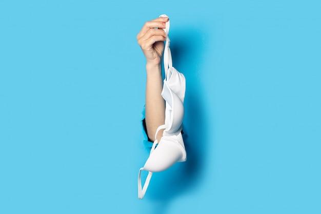 흰색 브래지어를 들고 파란색 찢어진 배경에 여성 손