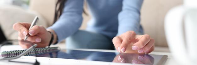 초침으로 태블릿에 여성 손으로 노트북 트위스트 작업에 펜으로 메모를 만들고