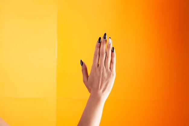 女性の手、オレンジ色の背景に手のひらを開く