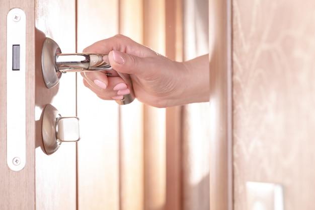 Женская рука, открывающая дверь