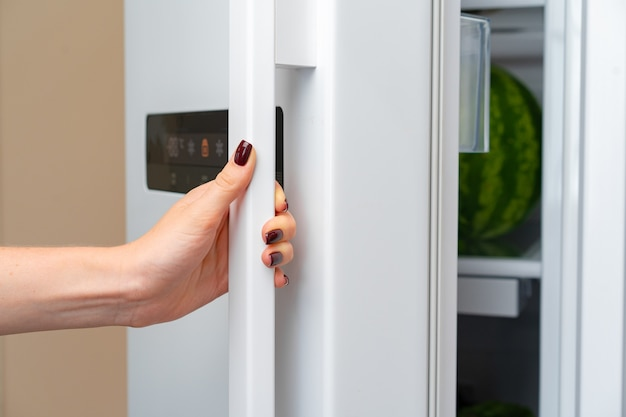 Female hand opens door of a fridge