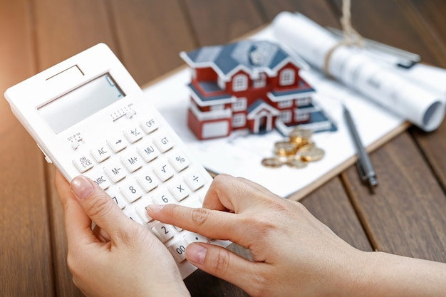 A female hand operating a calculator in front of a villa house model
