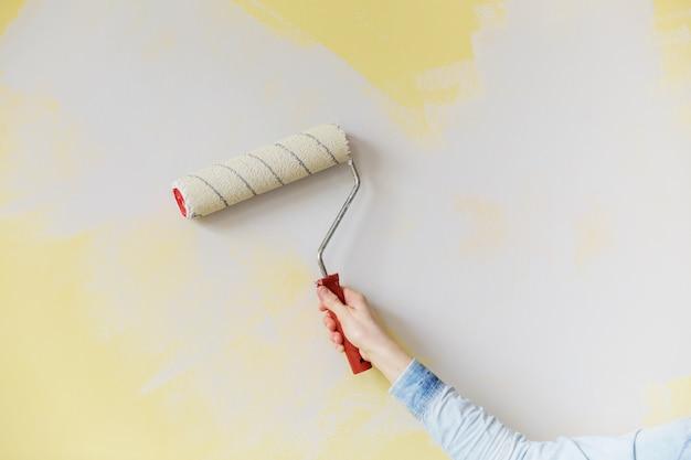 ペイントローラーと女性の手の絵画の壁