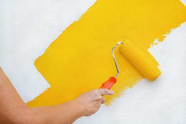 Женская рука красит стену желтой краской валиком Premium Фотографии