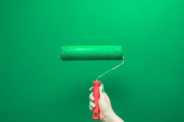 Женская рука красит стену валиком. ремонт зеленой краской