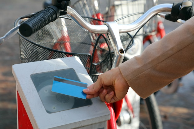 Female hand paying for bike with credit card, using modern contactless system at rental station outdoor