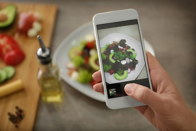 스마트 폰으로 음식을 촬영하는 여성 손