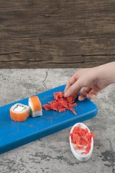 青いまな板から漬け生姜を摘む女性の手