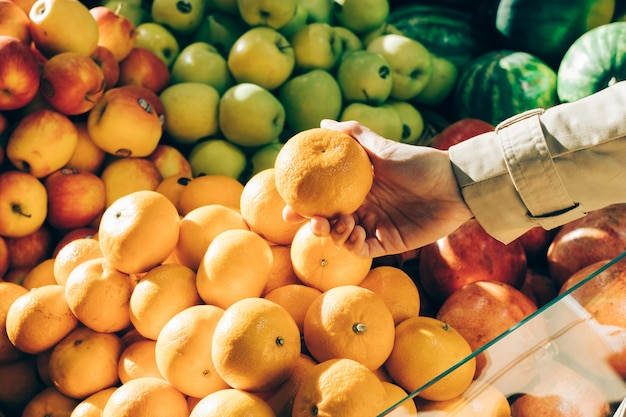 Female hand picks the oranges at the store