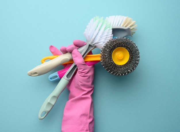 Female hand in a pink glove holds a stack of plastic cleaning brushes, blue background