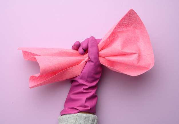 Female hand in a pink rubber glove holds a pink cleaning rag on a purple wall, close up
