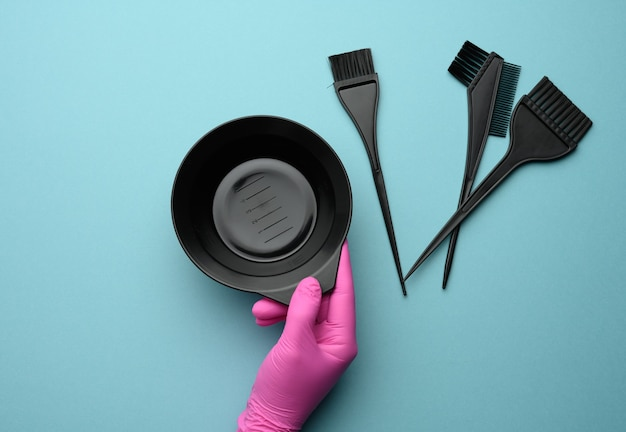 Female hand in a pink rubber glove holds plastic accessories for dyeing hair on a blue background, top view