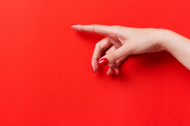 Female hand pointing finger to a red background. place for text