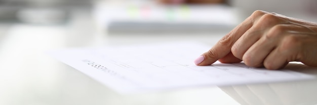 여성 손 사무실 근접 촬영에서 테이블에 문서에 줄에 손가락을 가리 킵니다. 홈 스쿨링 개념.