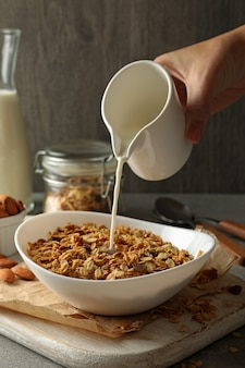 Female hand pour milk in bowl with granola