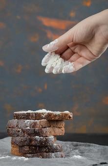 Женская рука наливает щепотку муки на хлеб.