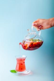 Женская рука наливает фруктовый чай из чайника в чашку
