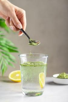 水のガラスに緑のスーパーフードの粉を注ぐ女性の手