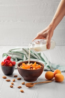 Female hand pouring milk in muesli with apricots and almonds