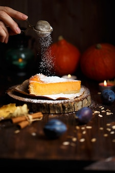 Female hand pouring a piece of pumpkin cheesecake with icing sugar, pumpkins