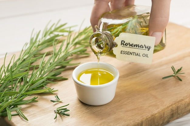 Female hand pouring rosemary essential oil