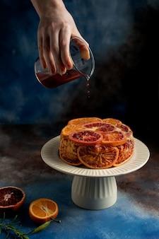 Женская рука наливает сироп на перевернутые кровяные апельсины, домашняя кухня