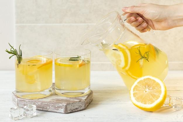 Женская рука наливает цитрусовый холодный лимонад в стаканы, летние напитки в жаркую погоду